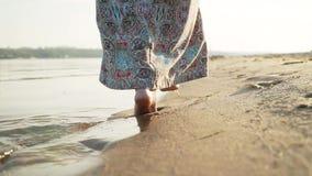 Cena bonita de uma mulher que anda na praia do oceano no por do sol filme