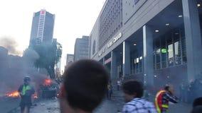 Cena caótica do motim com as bombas do fogo e de gás lacrimogêneo vídeos de arquivo