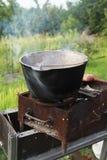 Cena che cucina su un fuoco aperto nel giardino Fotografia Stock