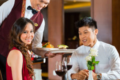 Cena china de la porción del camarero en restaurante u hotel elegante Foto de archivo libre de regalías