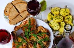 Cena con el vino, el pollo frito, las patatas y el pan Fotos de archivo libres de regalías