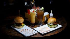 Cena con la hamburguesa grande y el jugo fresco Imagenes de archivo