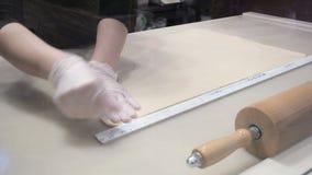 A cena: Cookaligns a folha da massa com uma r?gua, dando forma ? massa Produ??o de rolos de canela Produtos da padaria filme
