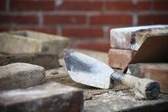 Cena da alvenaria com pá de pedreiro e tijolos imagem de stock royalty free