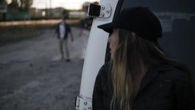 A cena da menina assustado corre longe do zombi, escondendo atrás da camionete branca Dois zombis assustadores que vêm para ela video estoque
