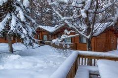 Cena da neve com cabanas rústicas de madeira imagem de stock