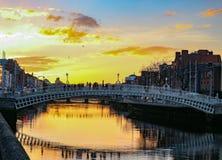 A cena da noite de Dublin com a ponte da moeda de um centavo do ` do Ha e o rio de Liffey ilumina-se Fotografia de Stock