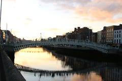 A cena da noite de Dublin com a ponte da moeda de um centavo do ` do Ha e o rio de Liffey ilumina-se ireland Fotos de Stock