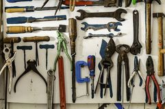 Cena da oficina Prateleira velha das ferramentas contra uma tabela e uma parede imagens de stock royalty free