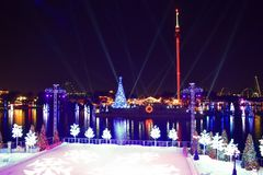 Cena da patinagem no gelo, árvores dos feriados e árvore de Natal colorida no lago e fundo de Sky Tower na área internacional da  fotografia de stock royalty free