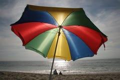 Cena da praia com proteção de oferecimento do guarda-chuva colorido de encontro a Sun e a chuva Imagens de Stock Royalty Free