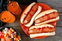 Cena da refeição de Dia das Bruxas com dedos, bebidas e doces do cachorro quente Foto de Stock Royalty Free