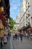 Cena da rua com as lojas de lembrança em Montmartre com uma vista da basílica de Sacre Coeur Foto de Stock