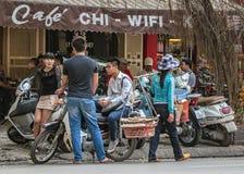 Cena da rua com os jovens que conversam e o vendedor de alimento na parte dianteira Imagens de Stock
