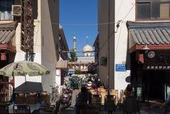 Cena da rua na cidade de Dunhuang, com povos em um stree e uma mesquita no fundo, em China Foto de Stock Royalty Free