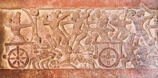 Cena de batalha com os guerreiros no vagões quatro-rodados, parede cinzelada dentro dos templos do século VII em Pattadakal, Índi Imagem de Stock Royalty Free