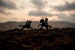 Cena de batalha medieval com cavalaria e infantaria Silhuetas das figuras como os objetos separados, luta entre guerreiros no fog fotografia de stock