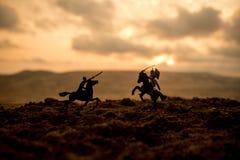 Cena de batalha medieval com cavalaria e infantaria Silhuetas das figuras como os objetos separados, luta entre guerreiros no fog foto de stock