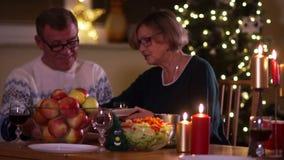 Cena de la familia en la Navidad El marido y la esposa mayores se están sentando en la tabla en acción de gracias La mujer pone l metrajes