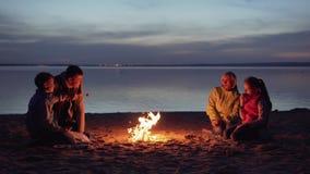 Cena de la familia por la hoguera en la playa en la noche almacen de metraje de vídeo