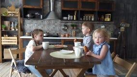 Cena de la familia: Tres niños en la tabla de cocina que comen los bollos y que beben té metrajes