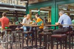 Cena de la gente ocupada en café al aire libre de la ciudad con las tablas y las sillas de madera altas Imágenes de archivo libres de regalías