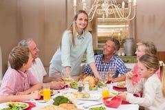 Cena de la Navidad de la porción de la mujer a su familia Imagen de archivo