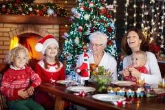 Cena de la Navidad Familia con los niños en el árbol de Navidad Foto de archivo