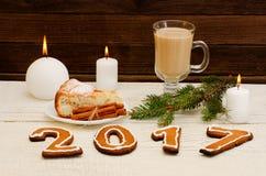 Cena de la Navidad, la figura en 2017 del pan de jengibre, empanada spruce de la rama, de la vela, del capuchino y de manzana Imagen de archivo