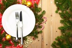 Cena de la Navidad - placa blanca con los cubiertos en fondo de madera Foto de archivo libre de regalías