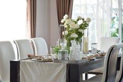 Cena de la tabla de madera y de sillas cómodas en hogar moderno Fotografía de archivo libre de regalías