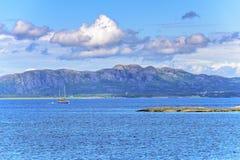 Cena de Serene Scandinavian Fjord Village com barco de navigação Foto de Stock Royalty Free