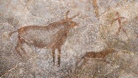 A cena de uma caça antiga em uma parede da caverna, feita com ocre foto de stock royalty free