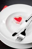 Cena del día de San Valentín con el ajuste de la tabla en ornamentos rojos y elegantes del corazón Imagenes de archivo
