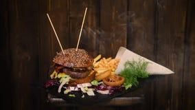 Cena deliziosa con il cheeseburger, le patatine fritte e gli anelli di cipolla video d archivio