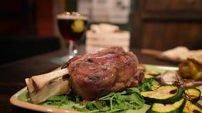 Cena deliziosa con lo stinco, le verdure e la birra della carne di maiale archivi video