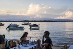 Cena della famiglia sulla spiaggia in Vourvourou, Grecia Immagini Stock