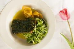Cena di color salmone su un piatto bianco con un tulipano rosa. Fotografie Stock Libere da Diritti