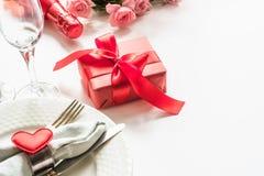 Cena di giorno di biglietti di S. Valentino con la regolazione di posto della tavola con il regalo rosso, vetro per champagne, un Fotografia Stock Libera da Diritti