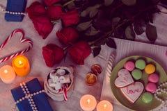 Cena di lume di candela con le rose rosse ed i regali Immagine Stock Libera da Diritti