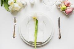 Cena di Pasqua Regolazione della Tabella con il tulipano bianco sulla tavola bianca Vista superiore fotografia stock