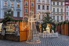 Cena do anjo com o chifre feito das festões das luzes, e da natividade em Praga, República Checa Imagem de Stock