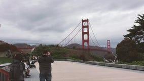 Cena do dia no centro de acolhimento de golden gate bridge em um dia nebuloso com os turistas que olham a ponte vídeos de arquivo