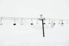 Cena do elevador de esqui com assentos sobre a montanha da neve Imagens de Stock