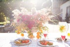 A cena do estilo de vida com a tabela mediterrânea bonita, colorida setup com flores e alimento foto de stock royalty free