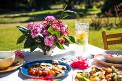 A cena do estilo de vida com a tabela mediterrânea bonita, colorida setup com flores e alimento fotos de stock royalty free