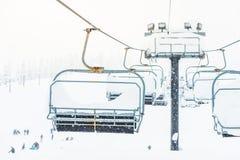 Cena do fim acima do elevador de esqui com os assentos que vão sobre o mounta da neve Foto de Stock