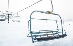 Cena do fim acima do elevador de esqui com os assentos que vão sobre o mounta da neve Imagens de Stock