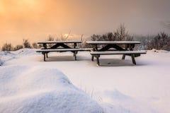 Cena do inverno com as tabelas e os bancos de piquenique cobertos de neve no nascer do sol imagens de stock royalty free