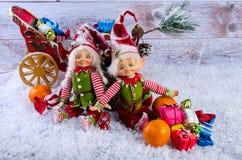 Cena do Natal com duendes, peúgas do Natal, tangerinas e presente Foto de Stock Royalty Free